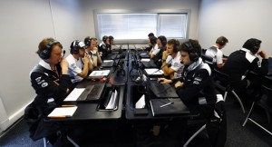 Jenson Button and Fernando Alonso study data with team members.
